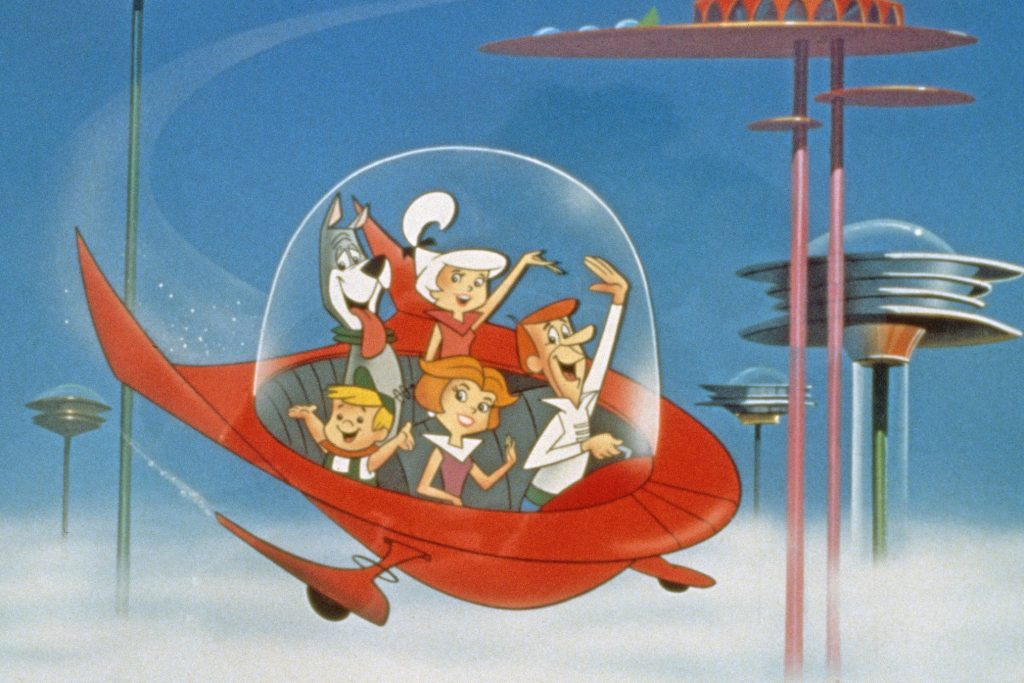 The Jetson family wave as they fly past buildings in space in their spaceship in a still from the animated television series, 'The Jetsons,' circa 1962. (Photo by Warner Bros./Courtesy of Getty Images)